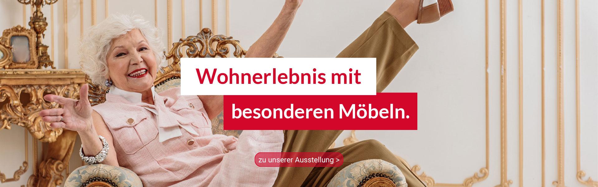 Wohnerlebnis mit besonderen Möbeln – ältere Dame sitzt vergnügt quer in ihrem gemütlichen Fernsehsessel