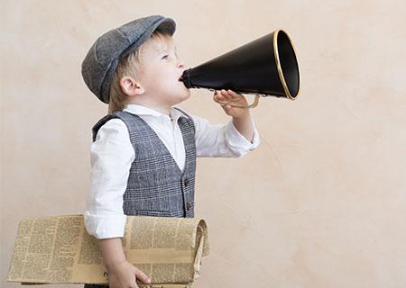 Kleiner Junge mit Sprachrohr verkündet aktuelle Angebote