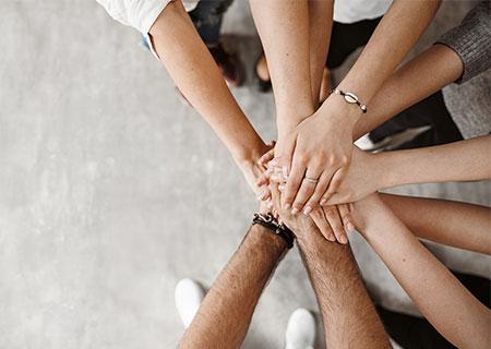 Ganz viele Hände mehrerer Personen übereinander gelegt von oben gesehen - unser Team ist stets für Sie da