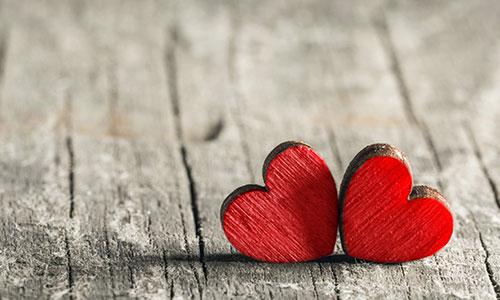 Zwei Herzen aus Holz auf Holzoberfläche, die einander berühren.