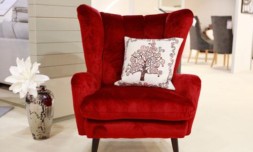 Bordeaux roter urgemütlicher Sessel mit Dekokissen und Vase in passender Farbe mit weißen Blumen darin.