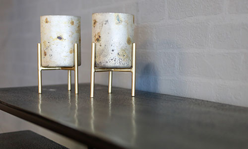 Zwei dekorative Teelichthalter aus weißem Milchglas mit Goldsprenkeln in goldener Halterung