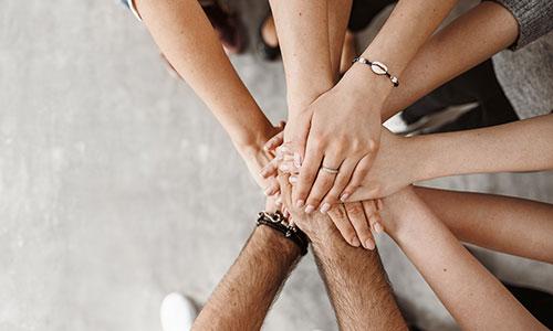 Starke Gemeinschaft - Bild mit übereinander gelegten Händen vieler Menschen.