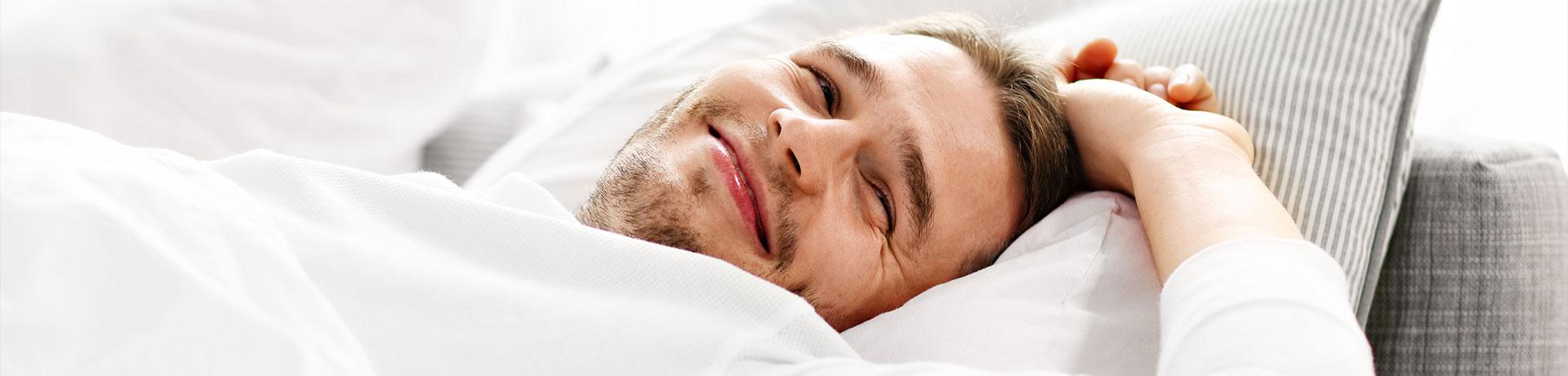 Mann wacht lächelnd auf im Bett