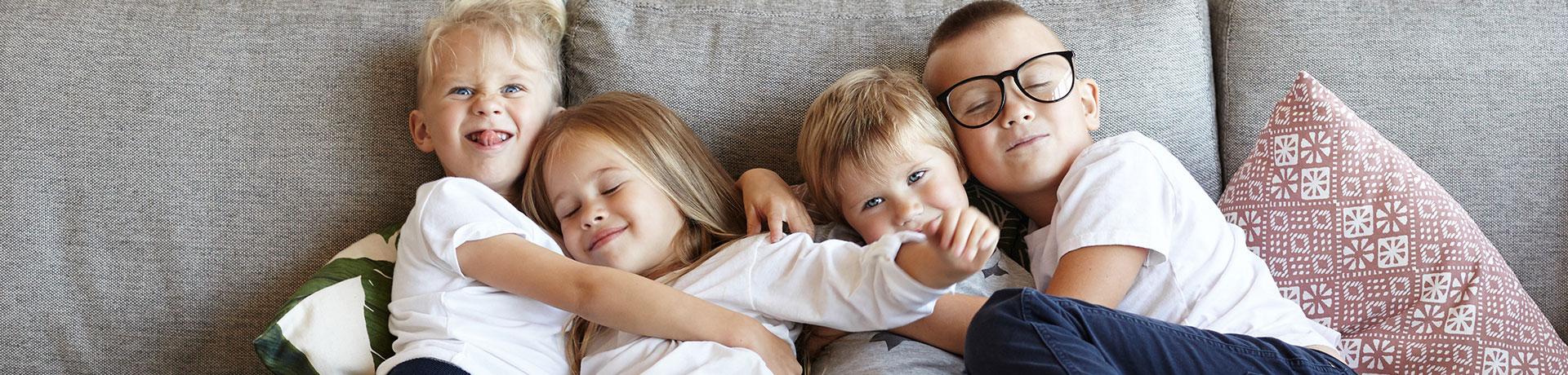 Vier Kinder auf einer bequemen Wohnlandschaft kuscheln miteinander