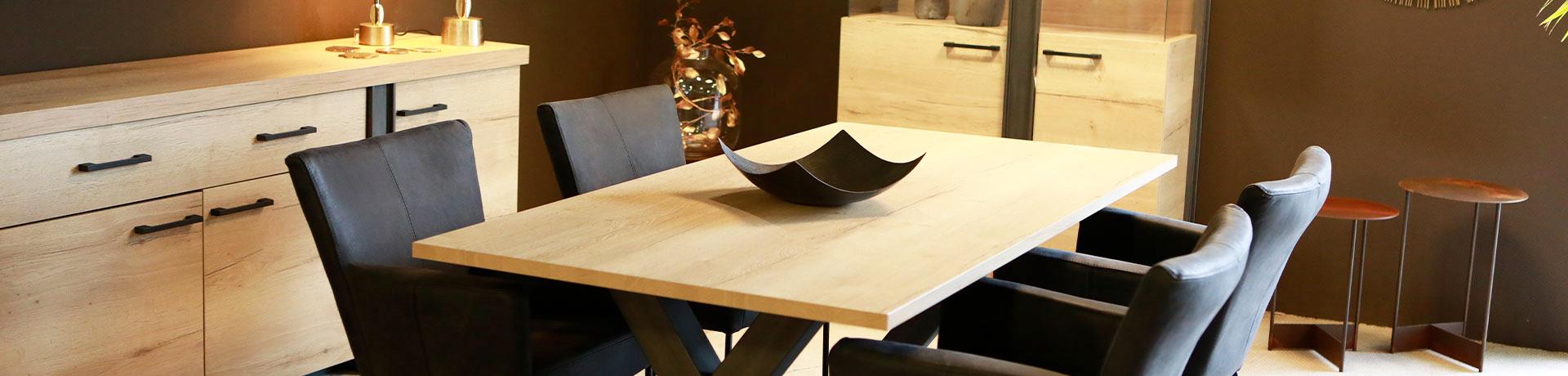 Essbereich mit Sideboard, Kommode und Esstisch aus hellem Holz mit bequemen Stühlen mit dunklem Bezug und farblich passender Schale als Deko auf dem Tisch.
